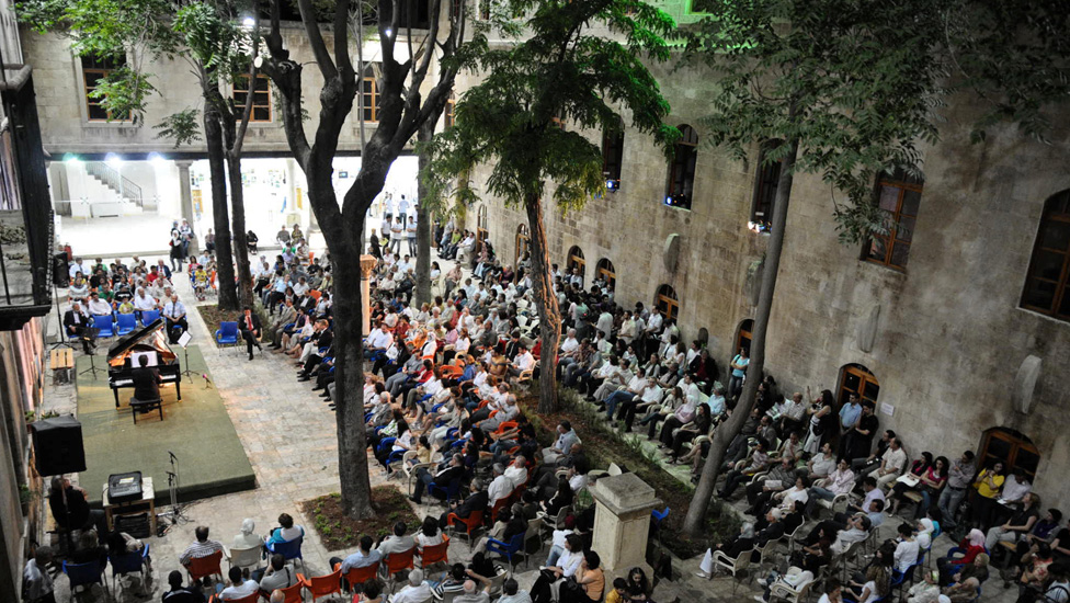 People attend a music concert in the school courtyard in June 2009