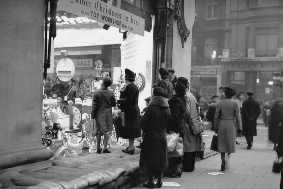 Shoppers stand on sandbags to look through shop windows in 1939