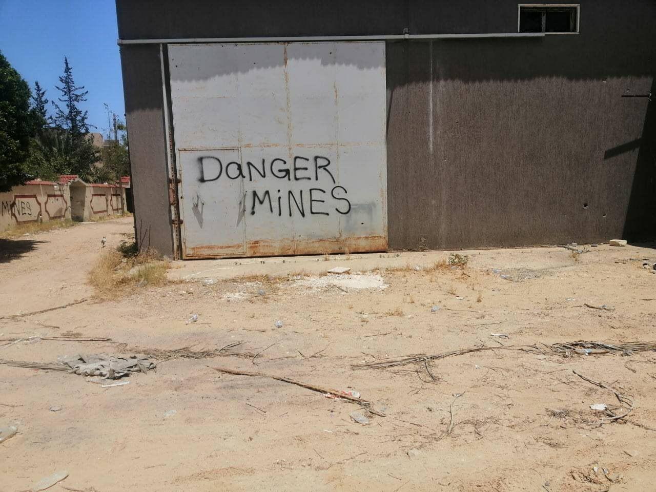 "The message ""Danger mines"" sprayed on a door"