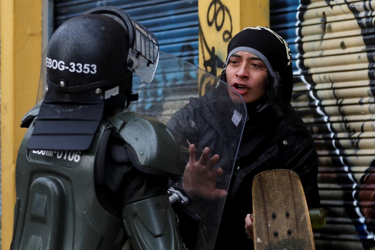A person talks to a police officer during a protest against the tax reform of President Ivan Duque's government in Bogota, Colombia, May 1, 2021.