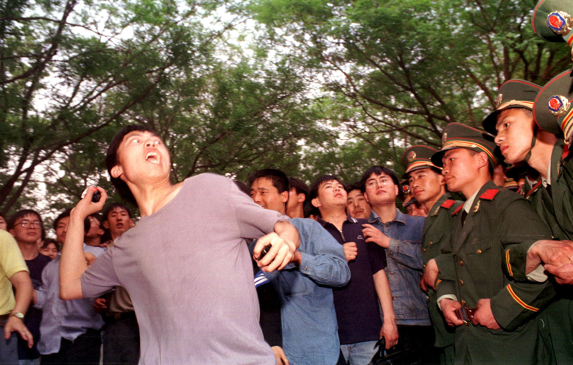 A university student throws a rock during a protest at the U.S. Embassy in Beijing May 9, 1999