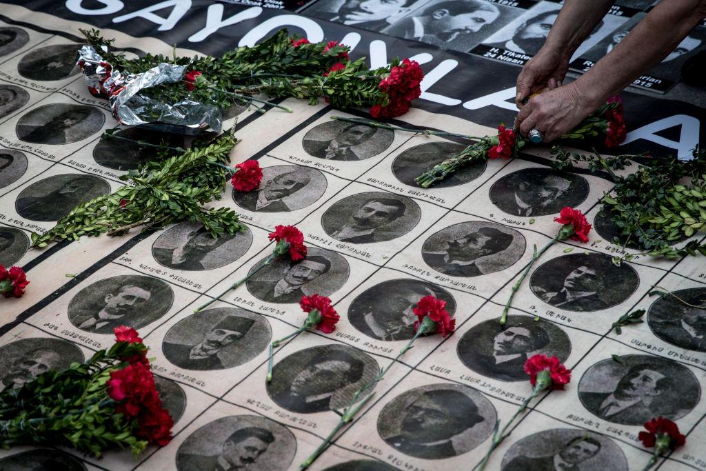 Personas dejando flores en el 103 aniversario del genocidio armenio.