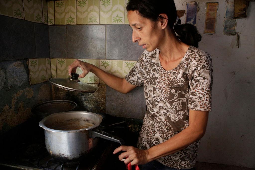 Mujer de bajos recursos cocinando.