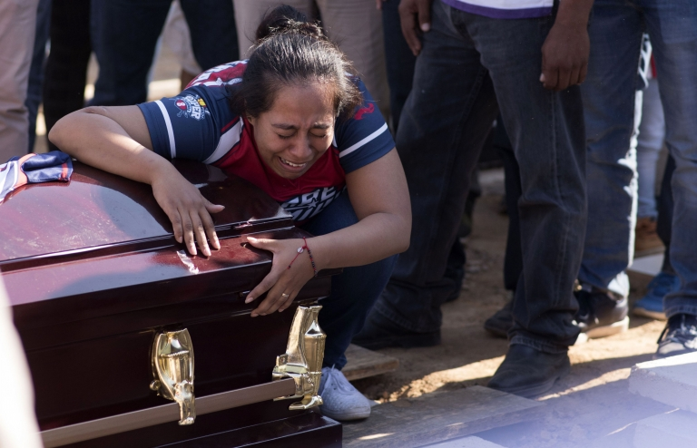 A woman cries as she mourns the victim of a shooting in Minatitlan in Mexico on 21 April 2019
