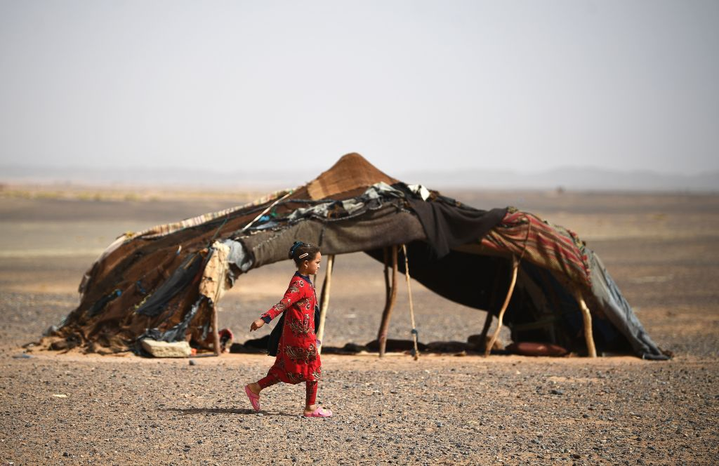 A girl walks past a tent in the Moroccan desert in May 2018