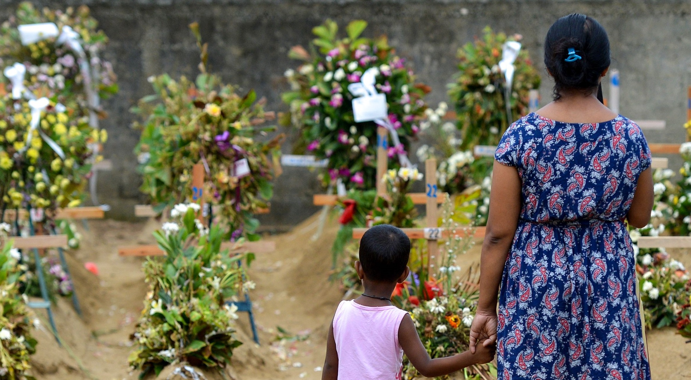 Relatives pay their respects in front of the graves of the victims of recent bomb blasts at St. Sebastian's Church in Negombo on April 28, 2019, a week after a series of bomb blast