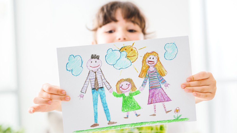 Image shows girl holding up a drawing of a family