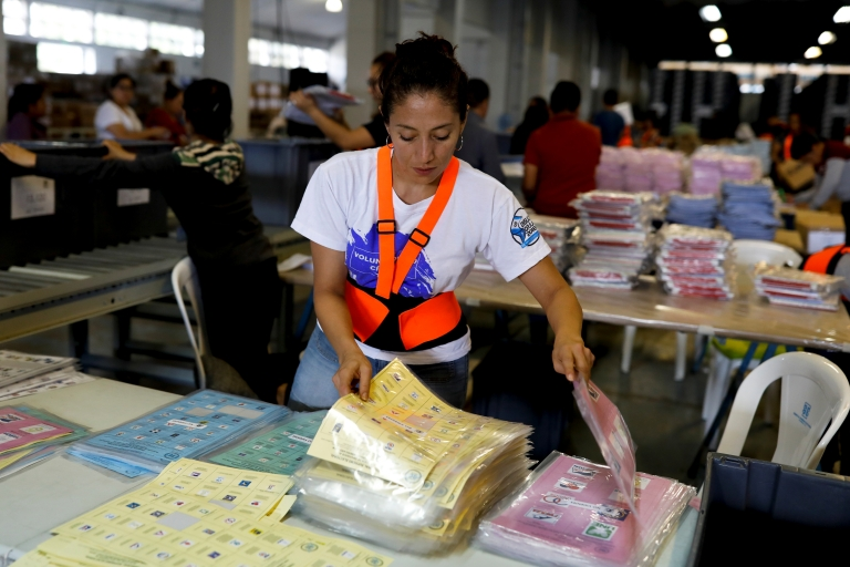 A woman sorts ballot papers at a warehouse in Guatemala City.