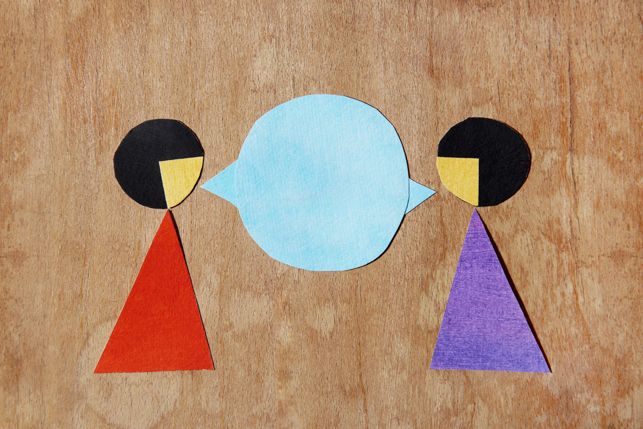 Some paper cutouts represent two women talking.
