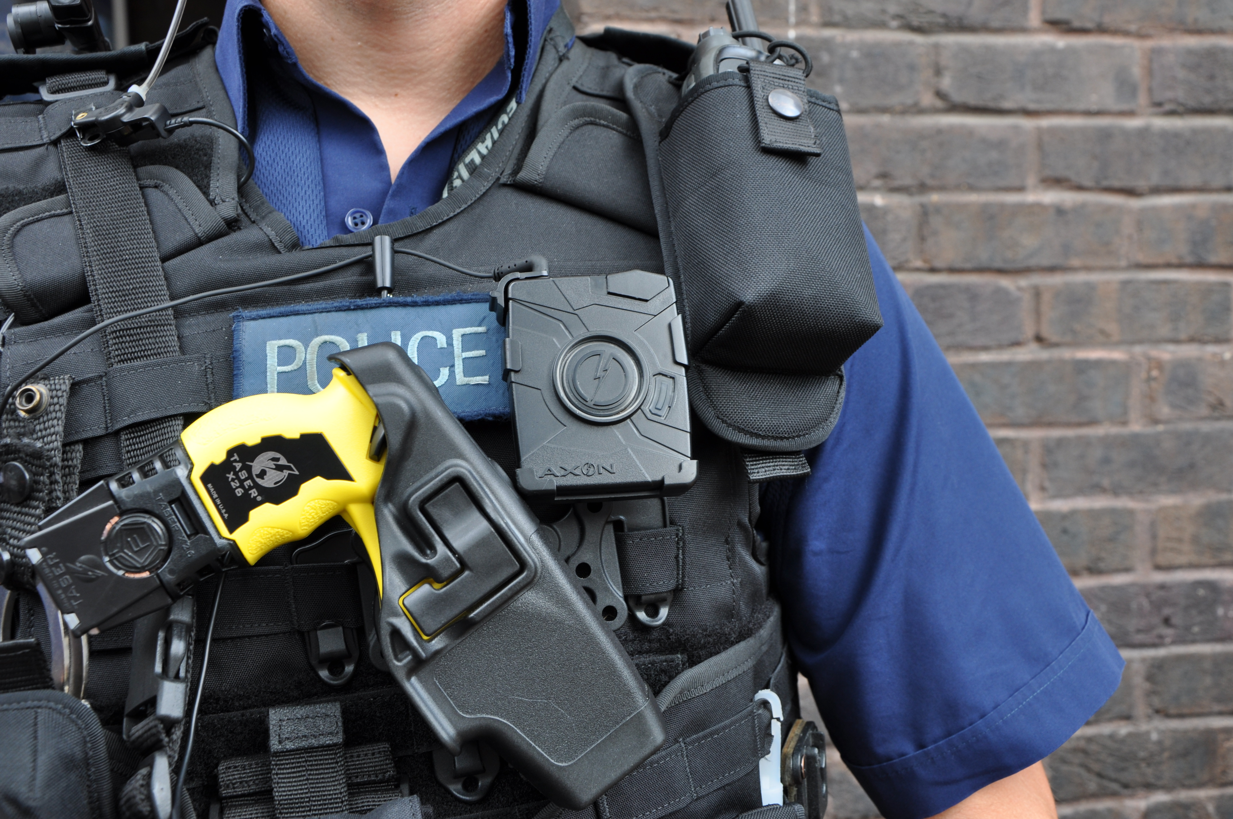 Armed British Police officer, with taser, wearing a body-worn video camera during operational trials
