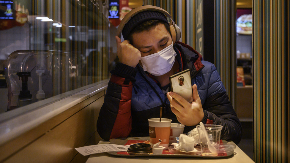 Man with a face mask checks phone while eating