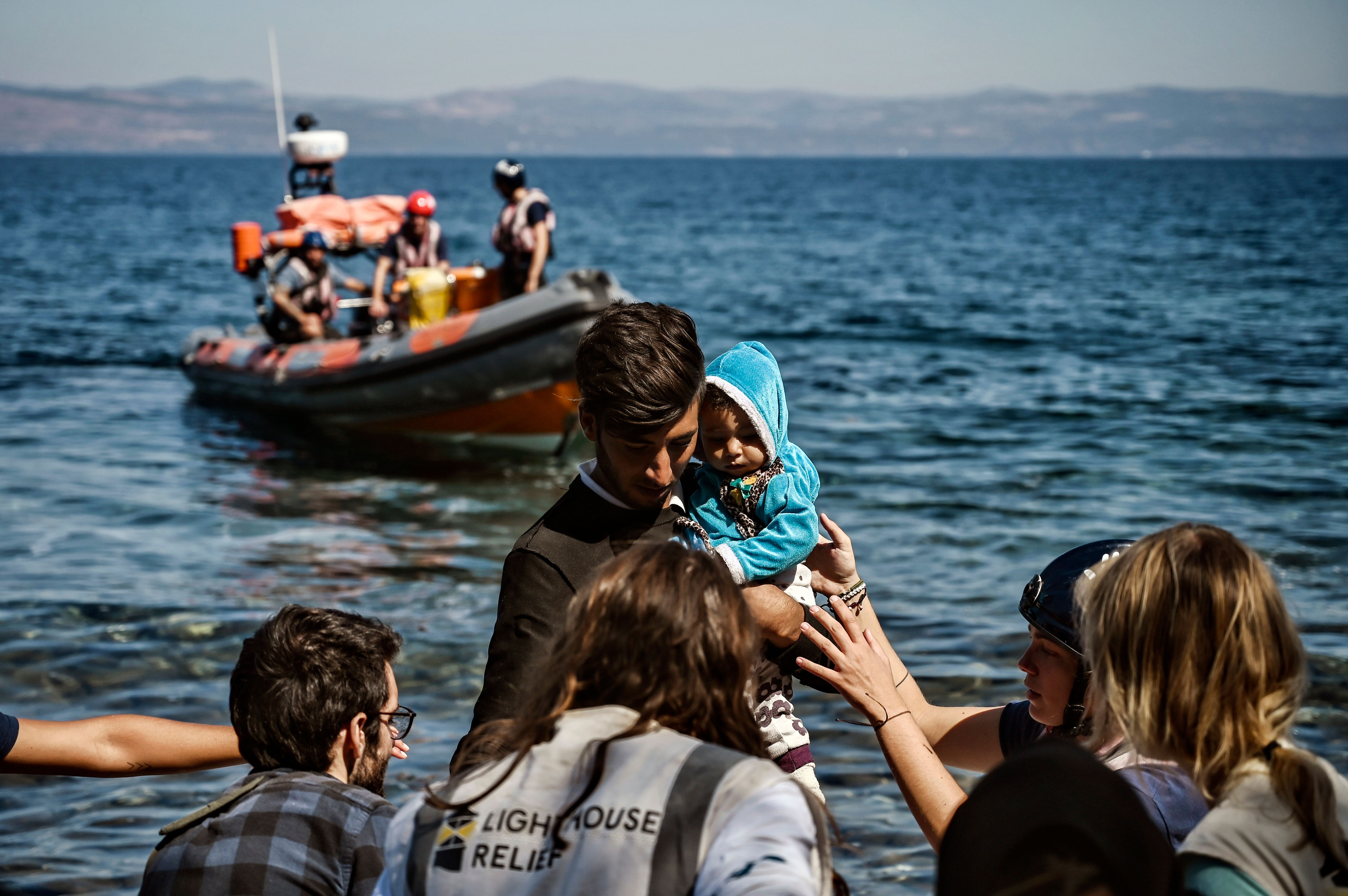 trump A migrant with a child is helped by rescuers as he arrives on the Greek island of Lesbos in September 2019