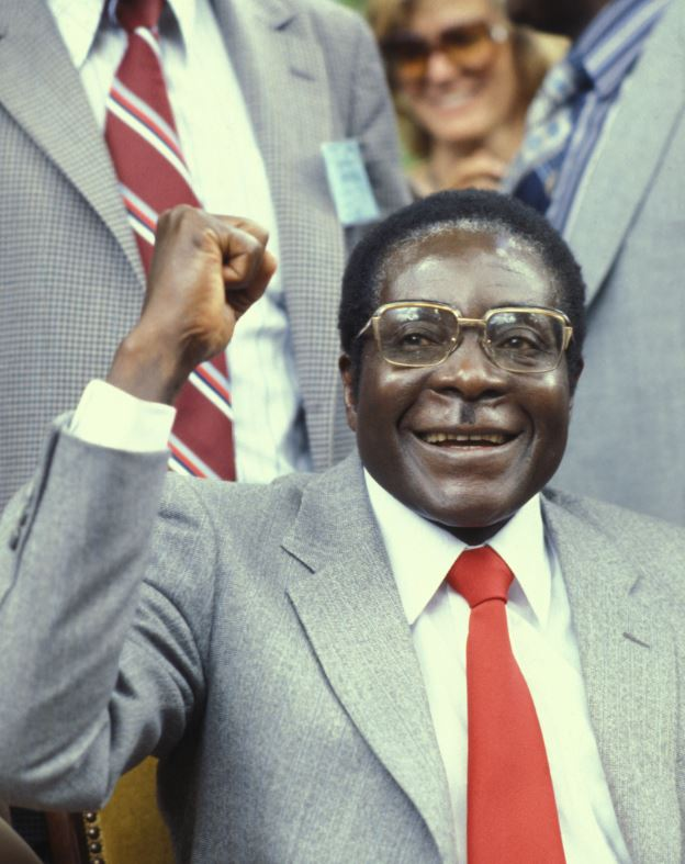 Robert Mugabe  smiles and holds fist in the air, in an image from 1980
