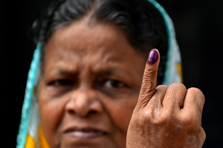 A Sri Lankan woman holds up her inked finger after casting her ballot at a polling station in Colombo on August 17, 2015