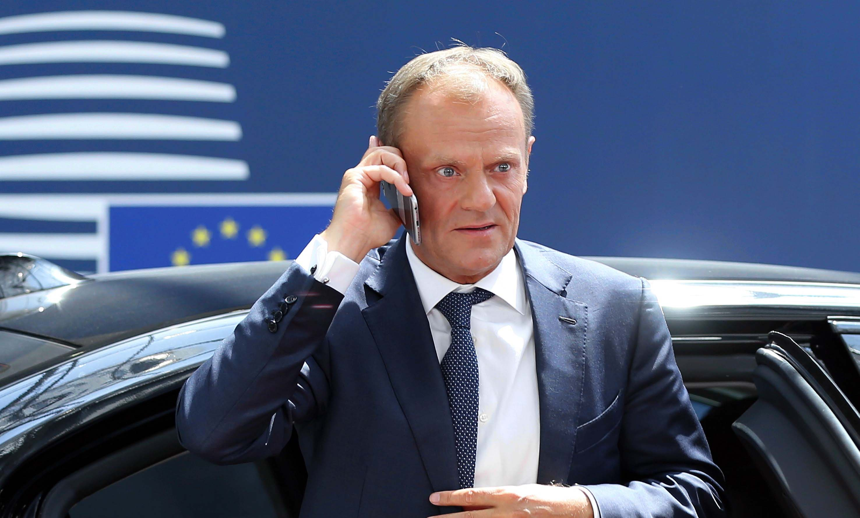 Donald Tusk on the phone at an EU summit