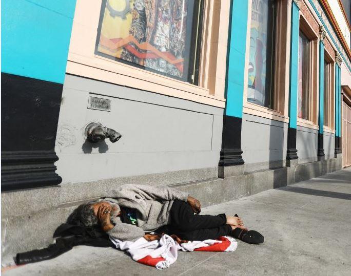 Homeless man lying in street in Los Angeles