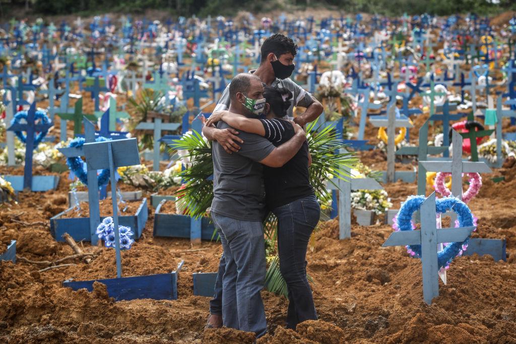 Gente abrazándose en un cementerio.