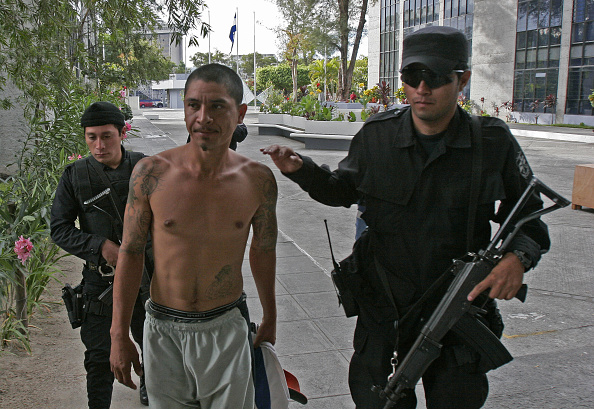 Un presunto criminal acompañado por oficiales policiales.