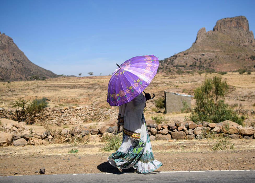 A woman walking with an umbrella along a road in Tigray, Ethiopia