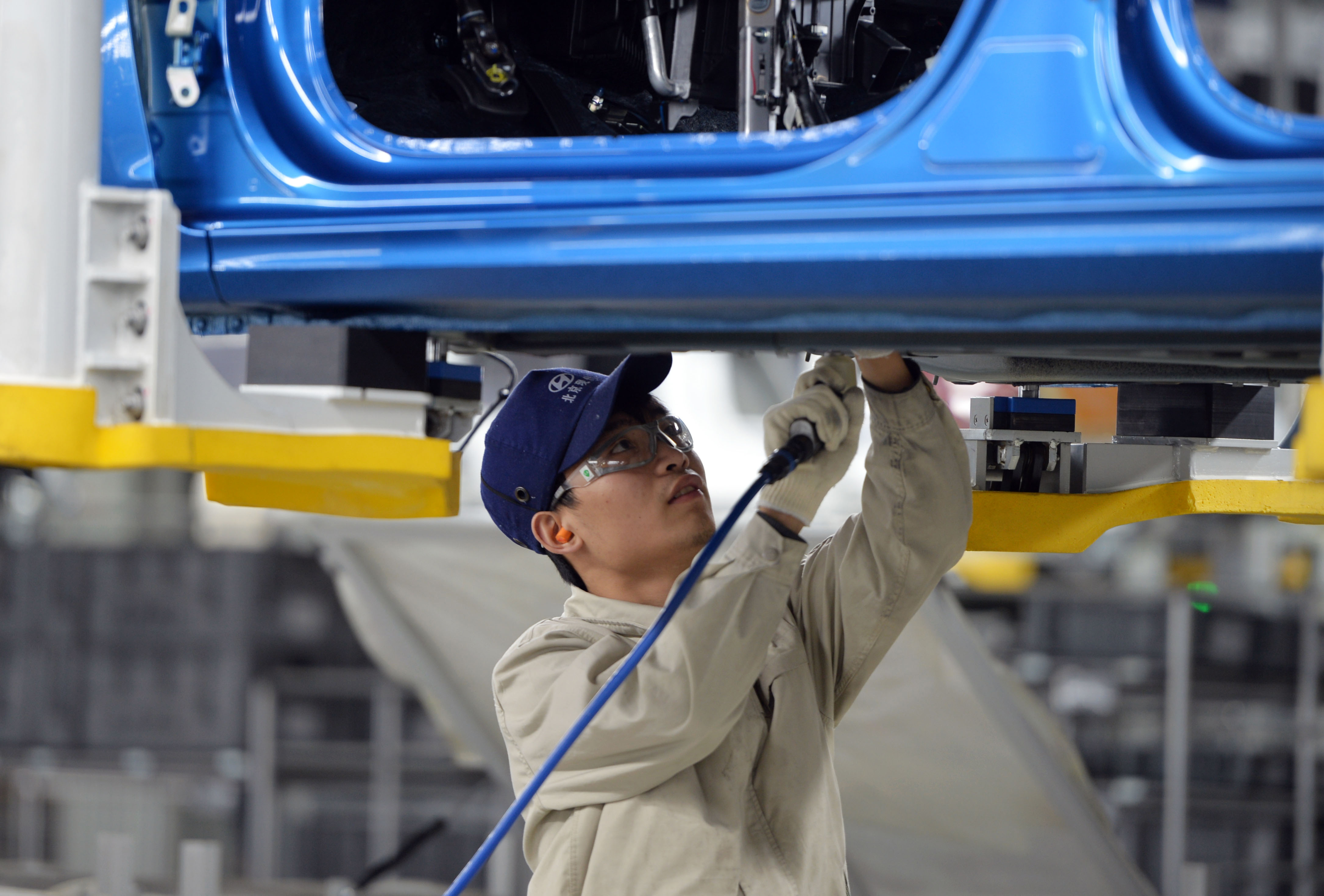 A worker in Hyundai's Cangzhou factory in China tightens screws on a vehicle.