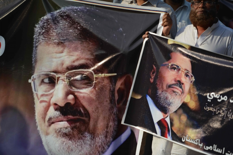 Activists of Jamaat-e-Islami hold pictures of former Egyptian President Mohamed Morsi during a symbolic funeral ceremony in Islamabad on 18 June 2019