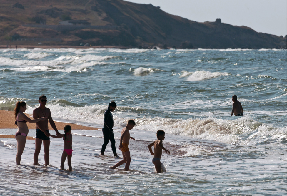 Beach-goers play at the water's edge