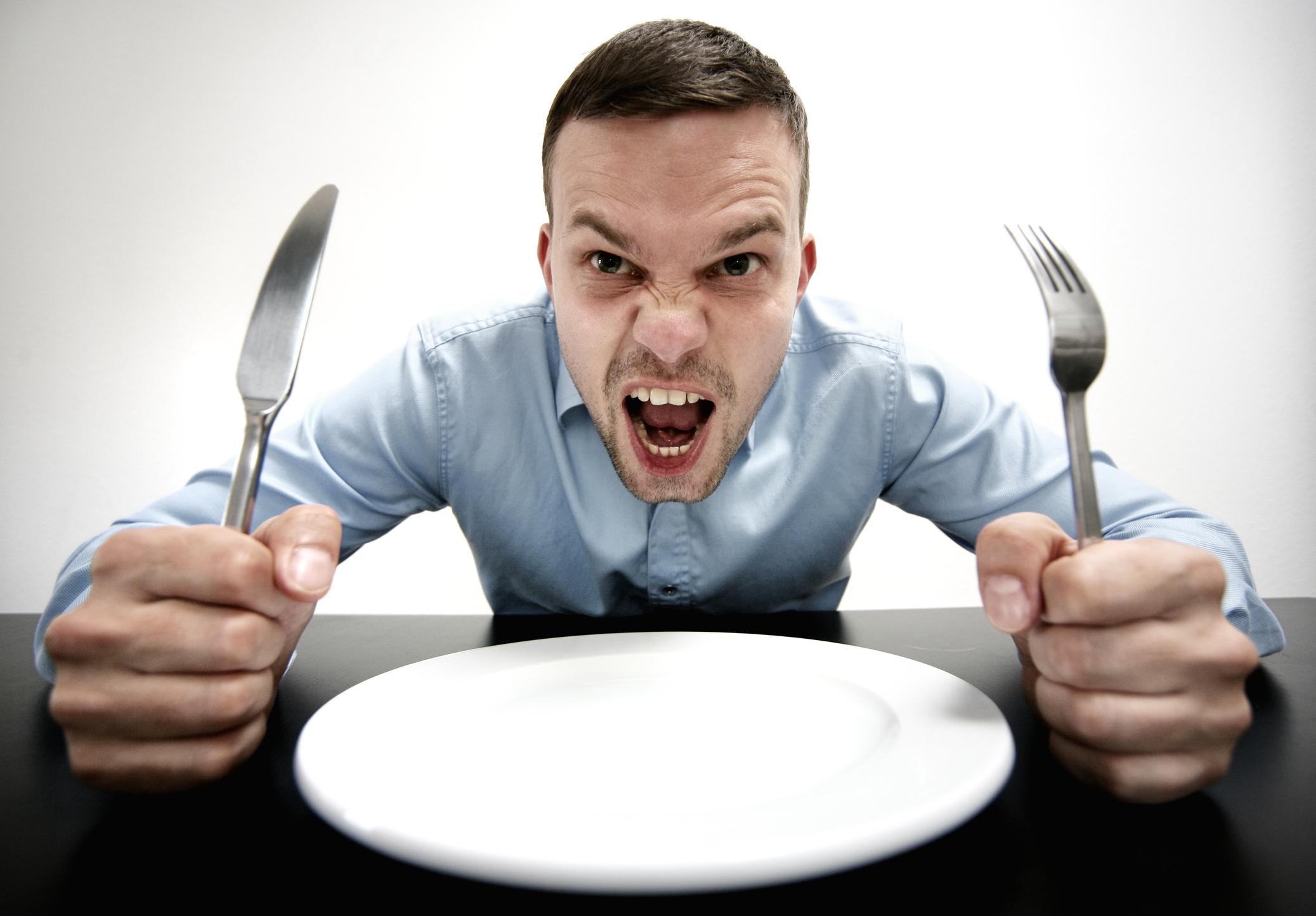 Hoimbre frente a un plato de comida vacío