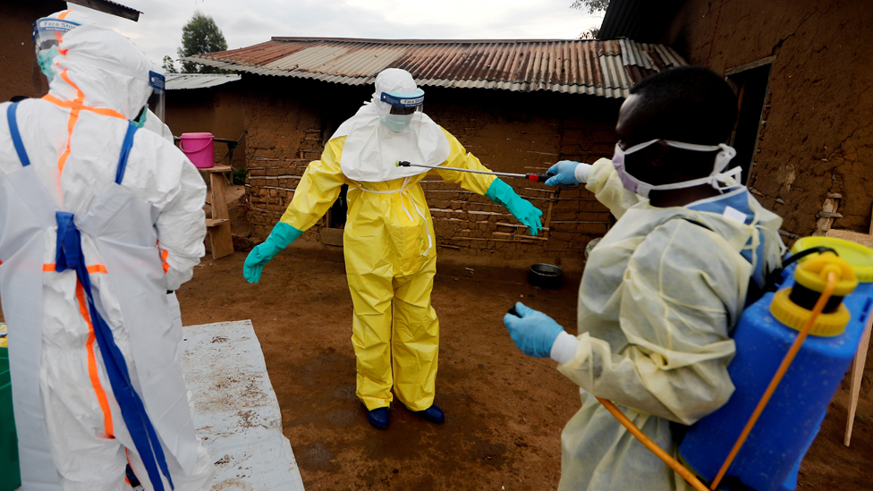 Kavota Mugisha Robert, a healthcare worker who volunteered in the Ebola response, decontaminates his colleague after he entered the house of 85-year-old woman