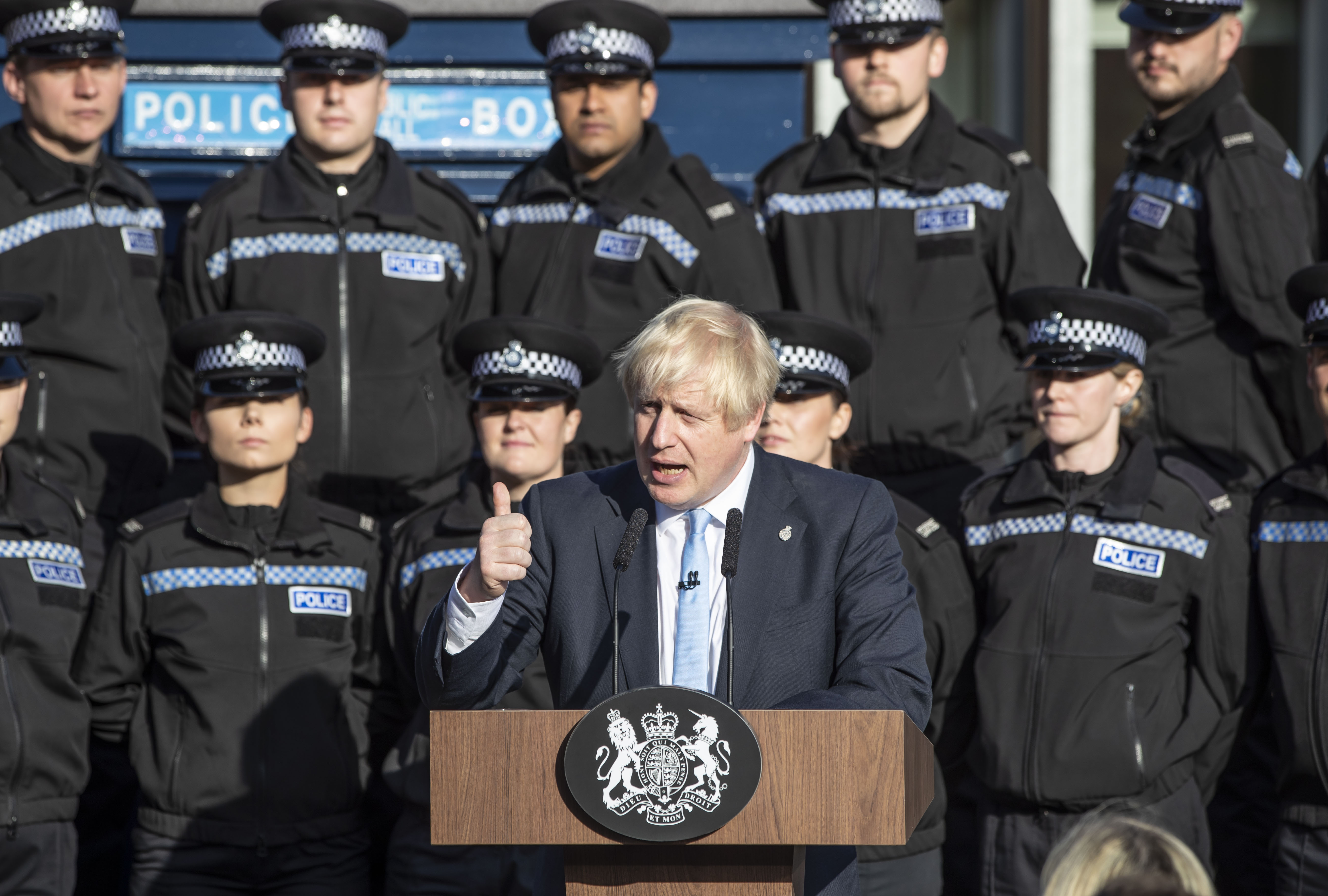 Boris Johnson standing in front of police officers