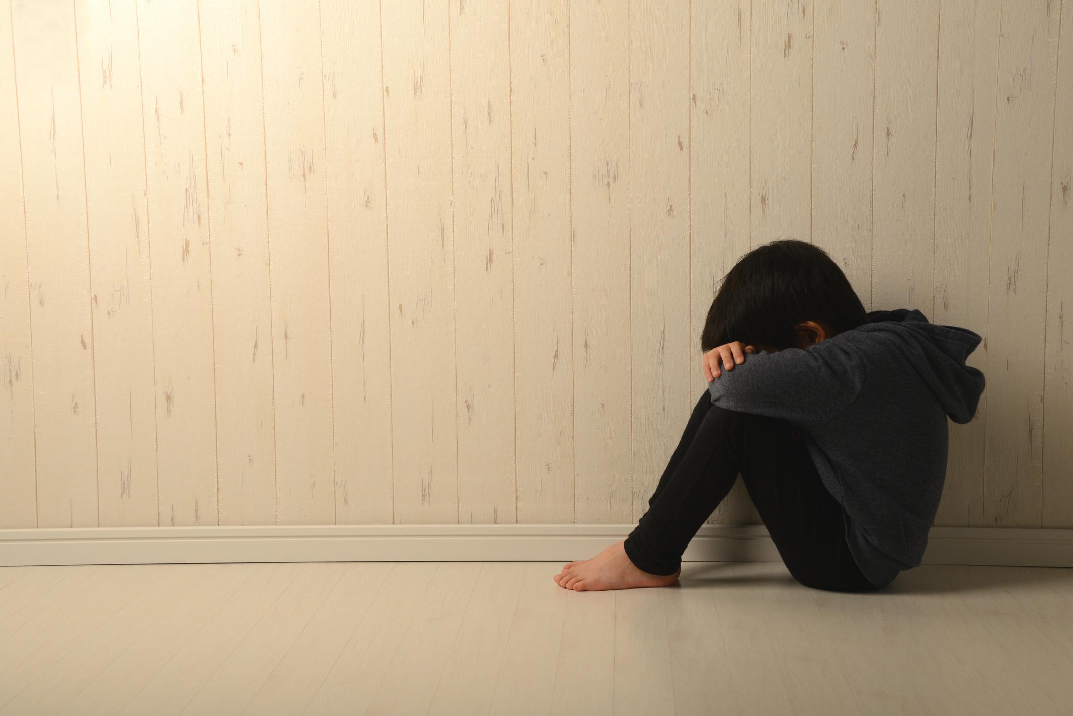 Suffering child in dark room - stock photo