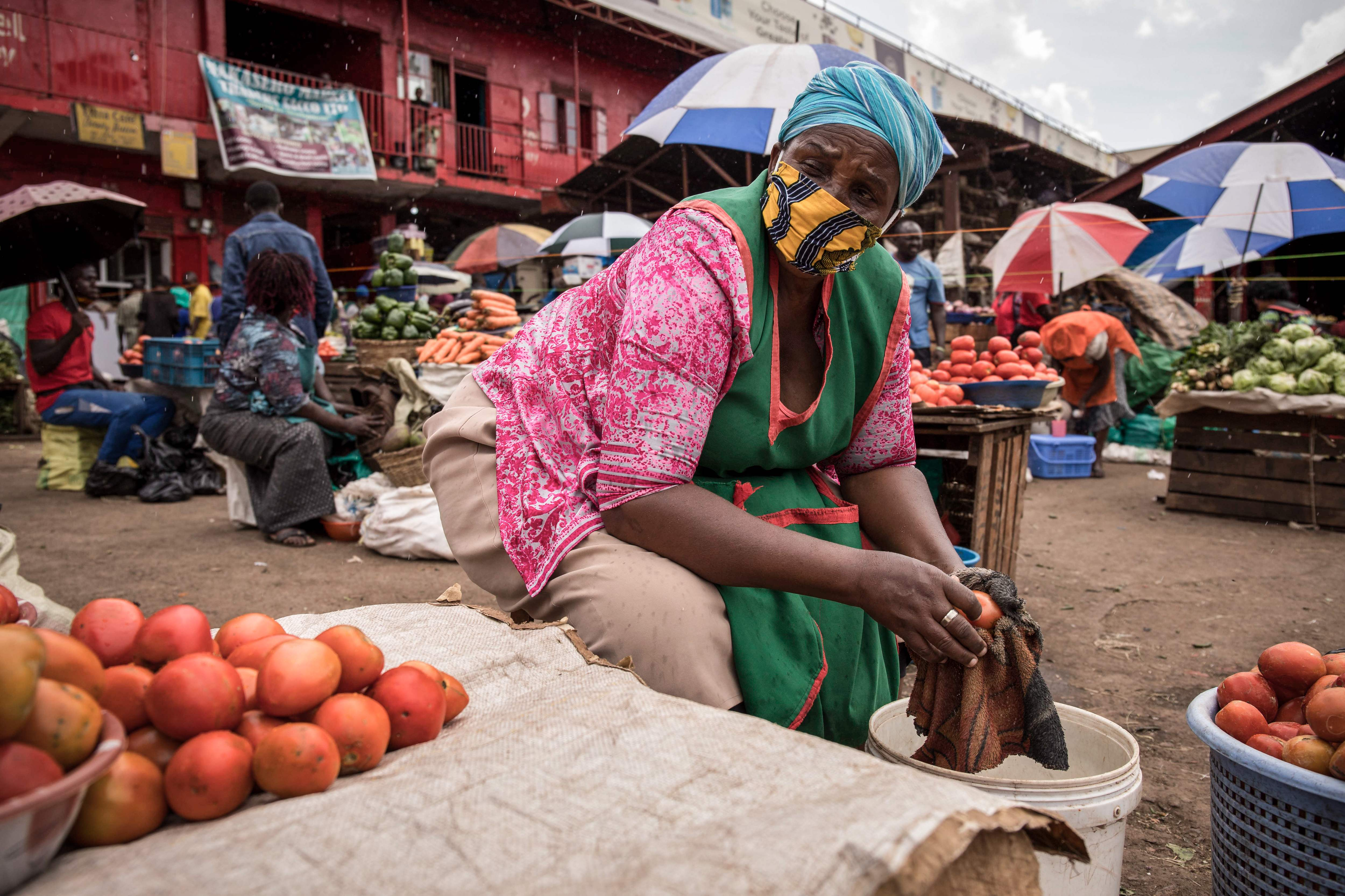 A woman sells tomatoes while wearing a face mask at the Nakasero market in Kampala, Uganda,