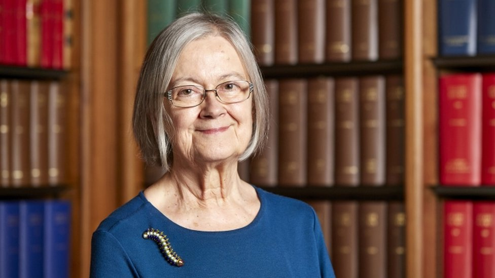 lady hale in front of a bookcase