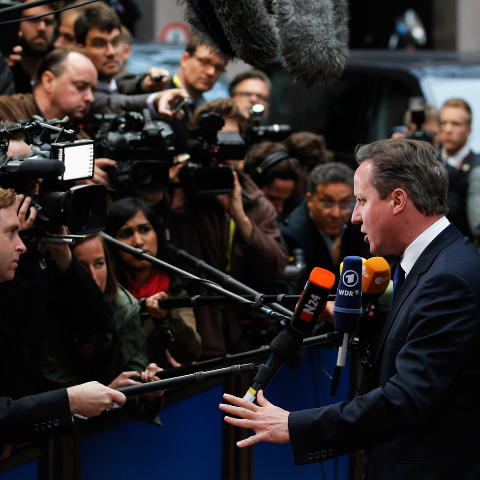 David Cameron speaking to a crowd of cameras and the media