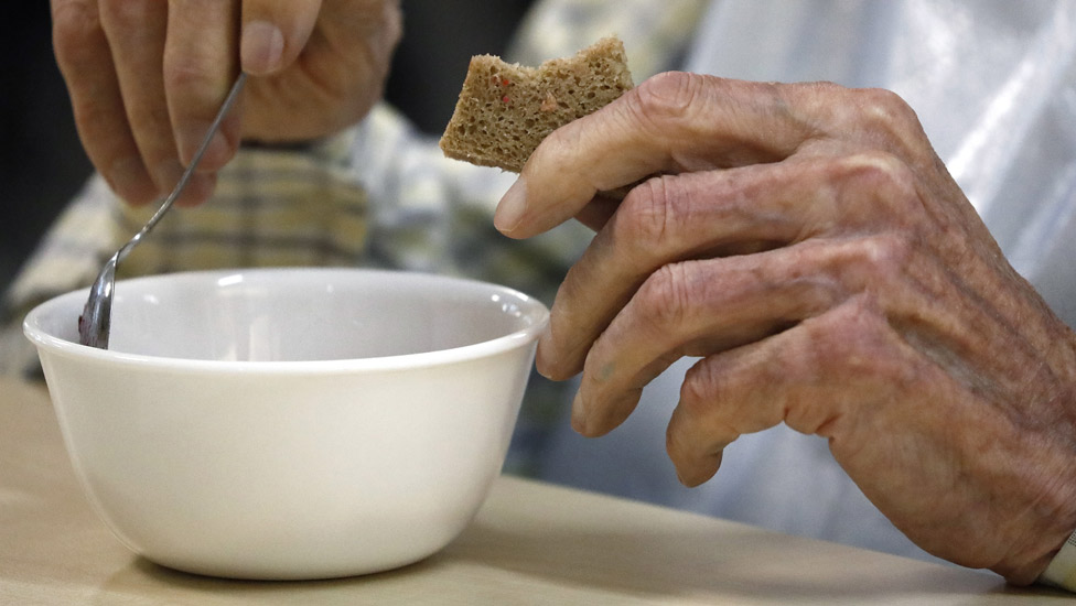Old person's hand holding a piece of bread and the other hand is holding a spoon over a bowl