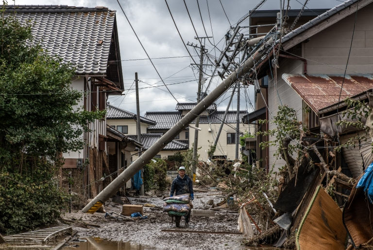 woman helps to clear up a shop that was flooded during Typhoon Hagibis, on October 15, 2019 in Hoyasu near Nagano, Japan