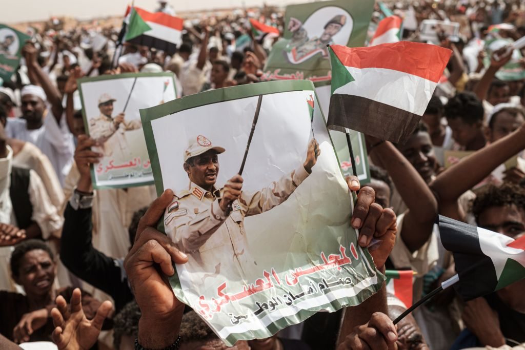Supporters hold portraits of Hemeti  before a rally in the village of Abraq, about 60km north-west of Khartoum, Sudan