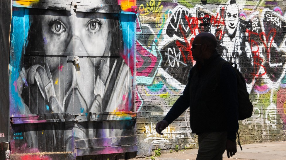 A pedestrian walks past a mural of a woman wearing a facial mask