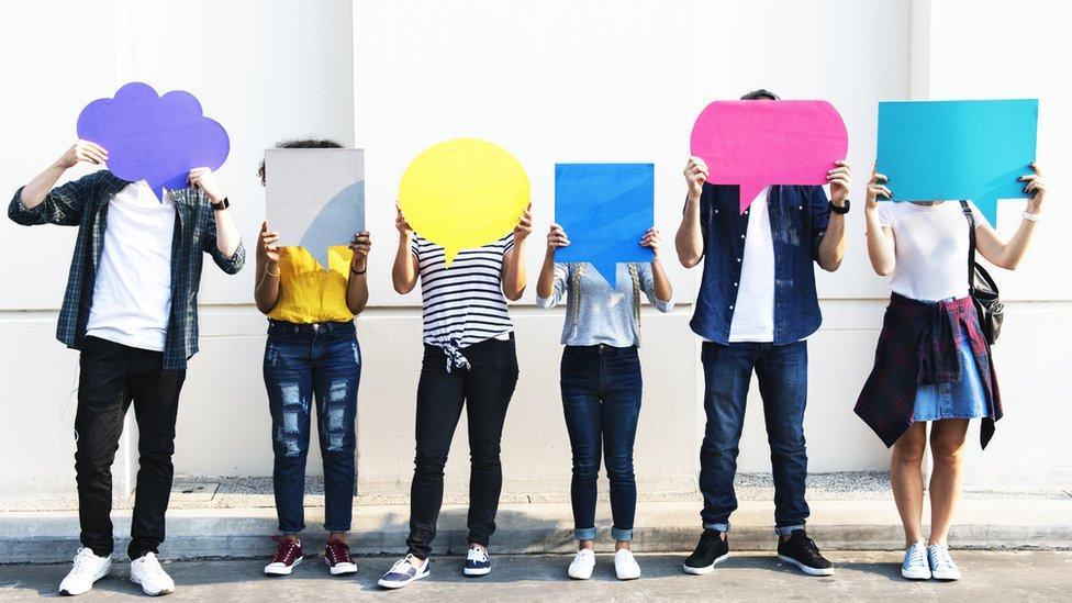 Una fila de personas están paradas una al lado de la otra con cartulinas que simulan nubes de conversación como las de los cómics