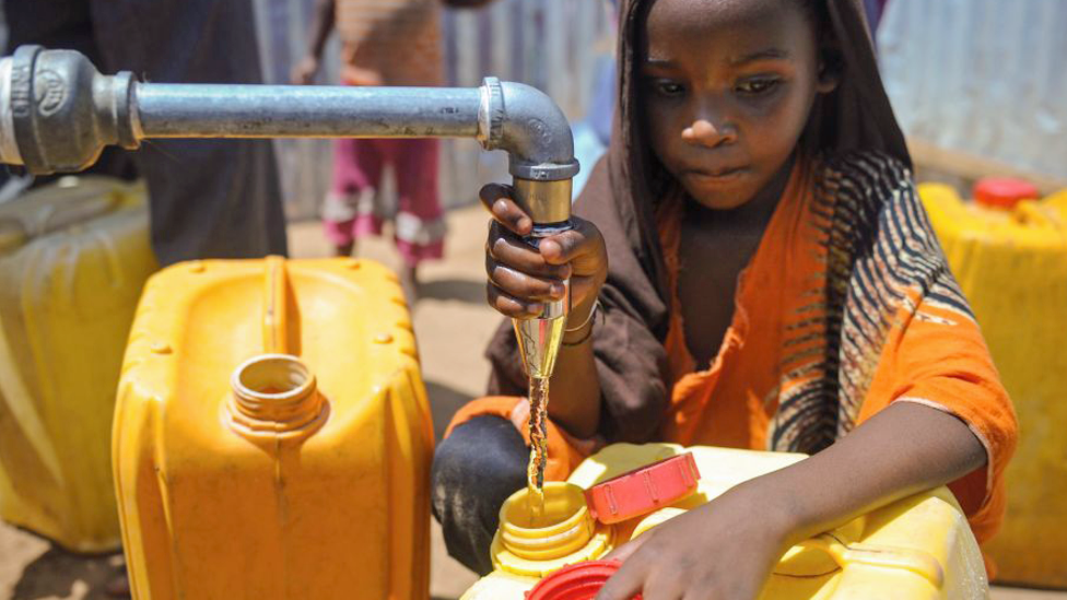 A Somali girl collects water from a well at a camp on the outskirts of Mogadishu, Somalia - March 2018