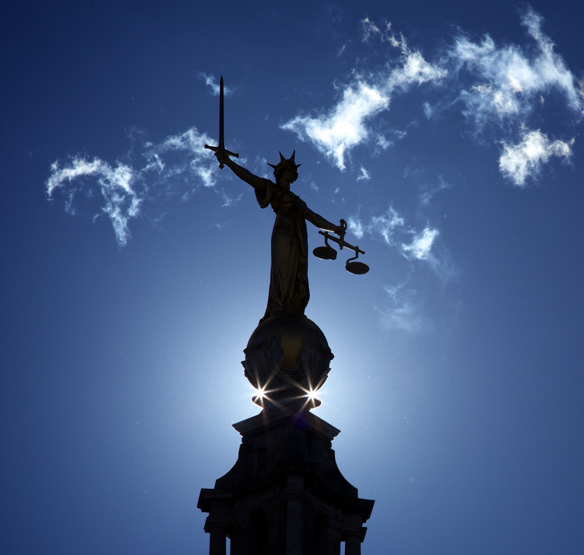 A statue of justice silhouetted against the sky.