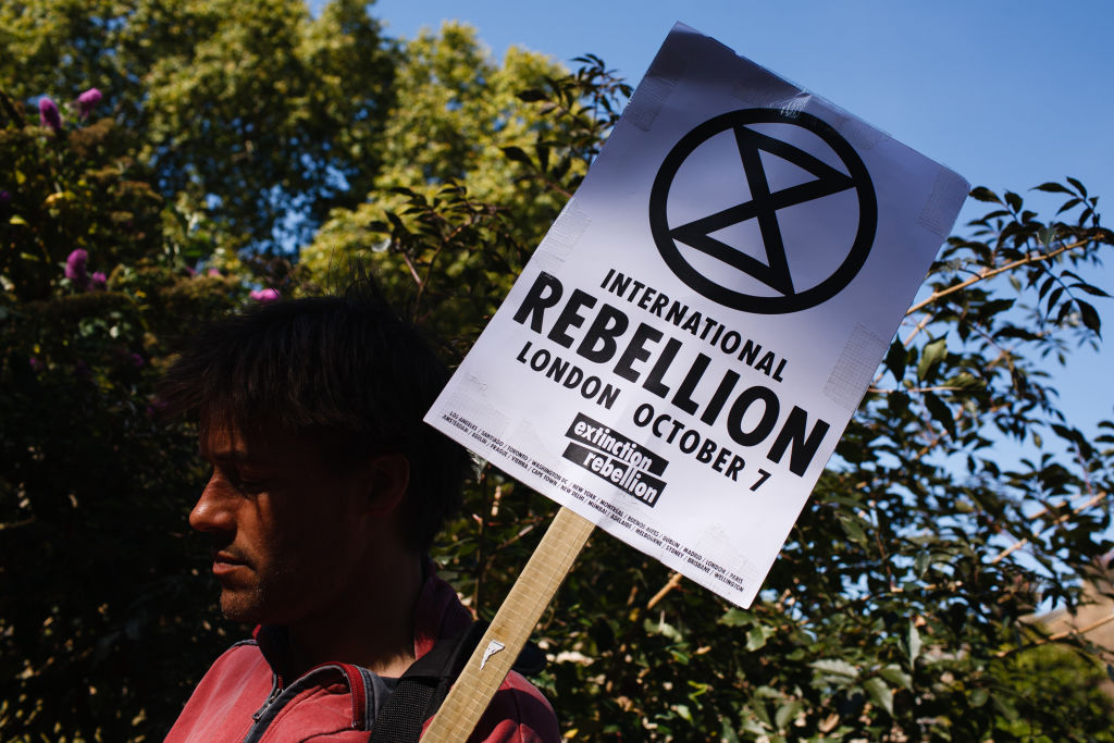 Man holding a Extinction Rebellion placard