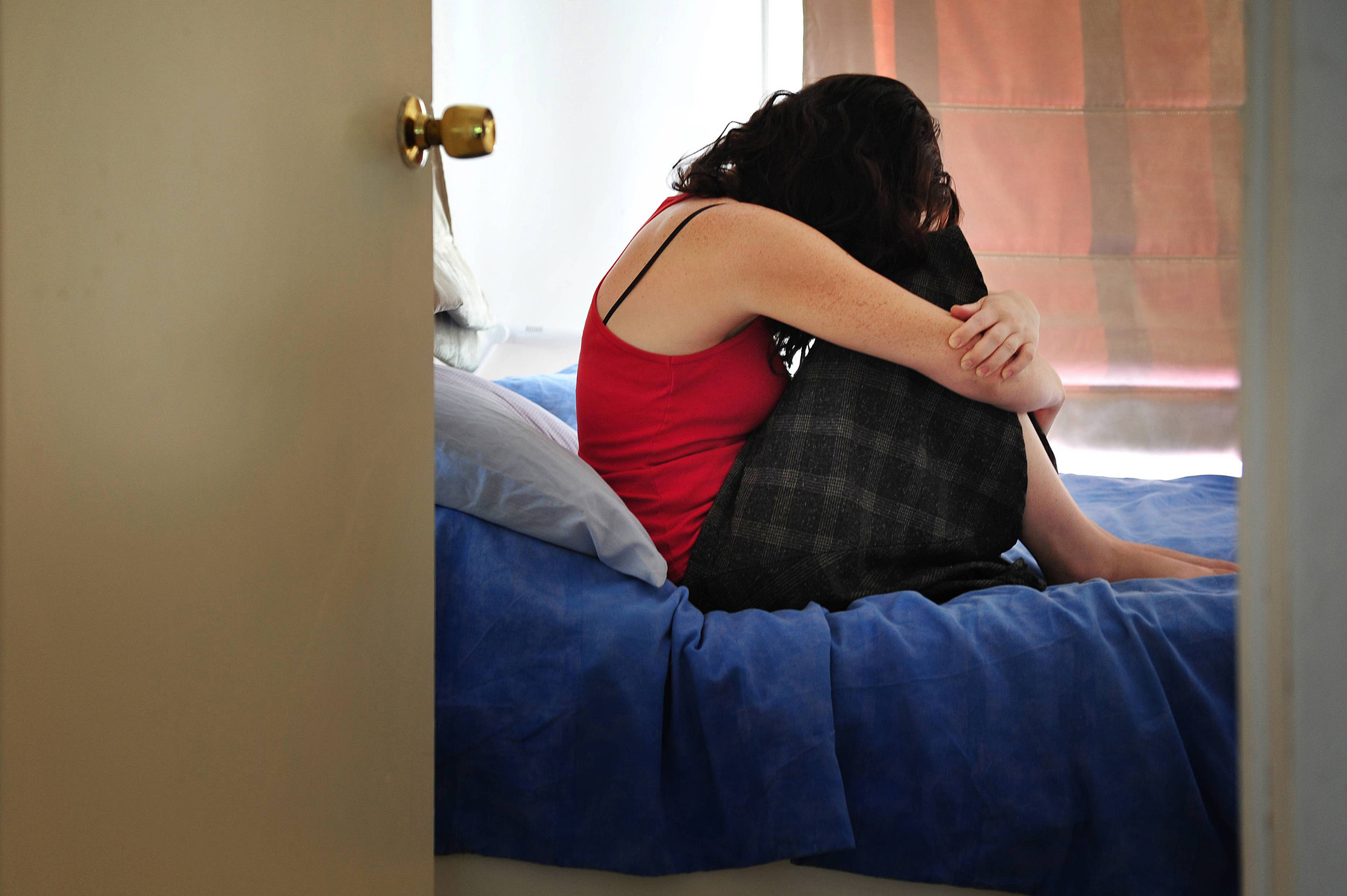 Depressed young woman sitting on the bed at home suffering from a severe depression
