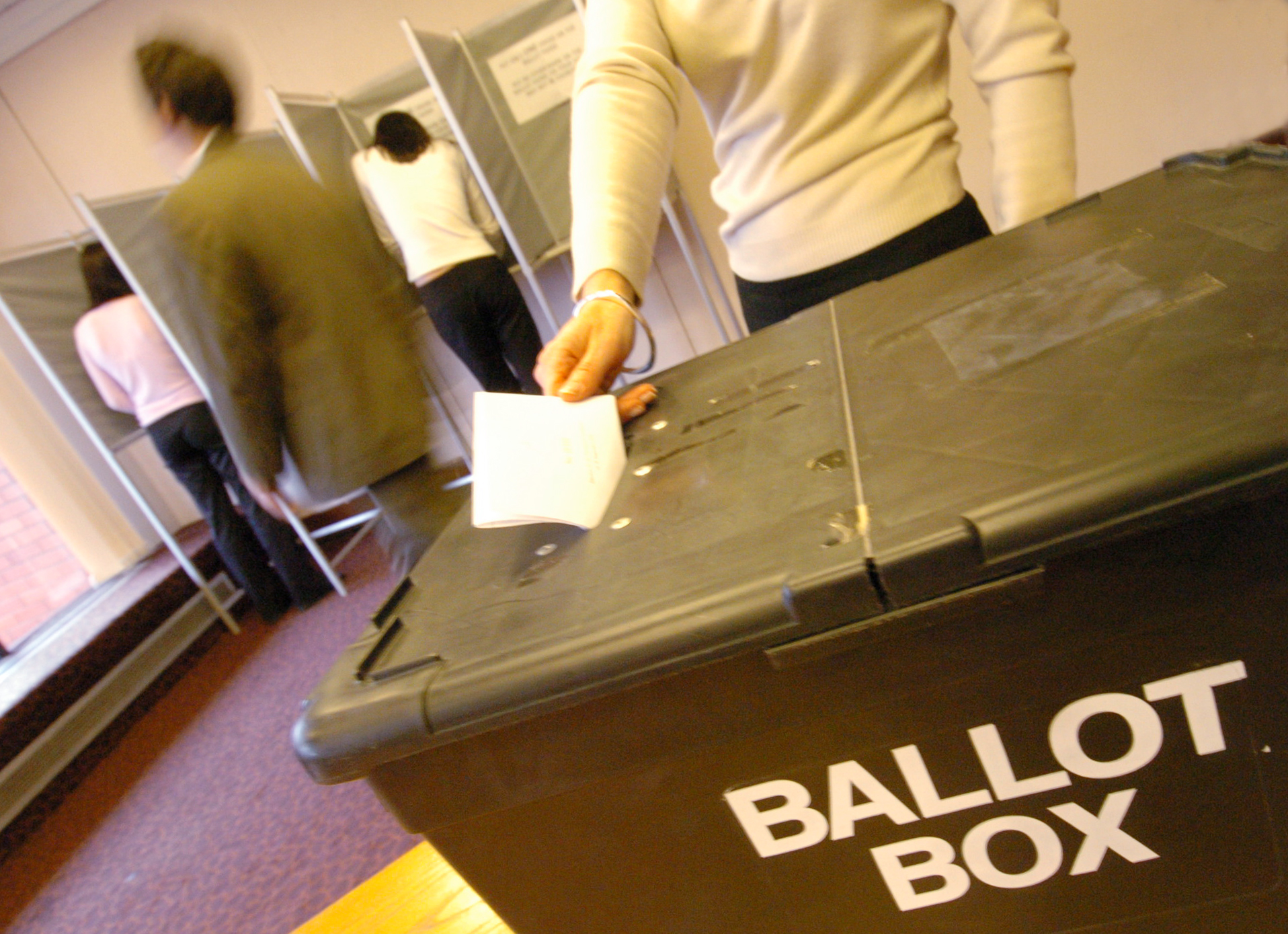 Woman placing vote in ballot box at election