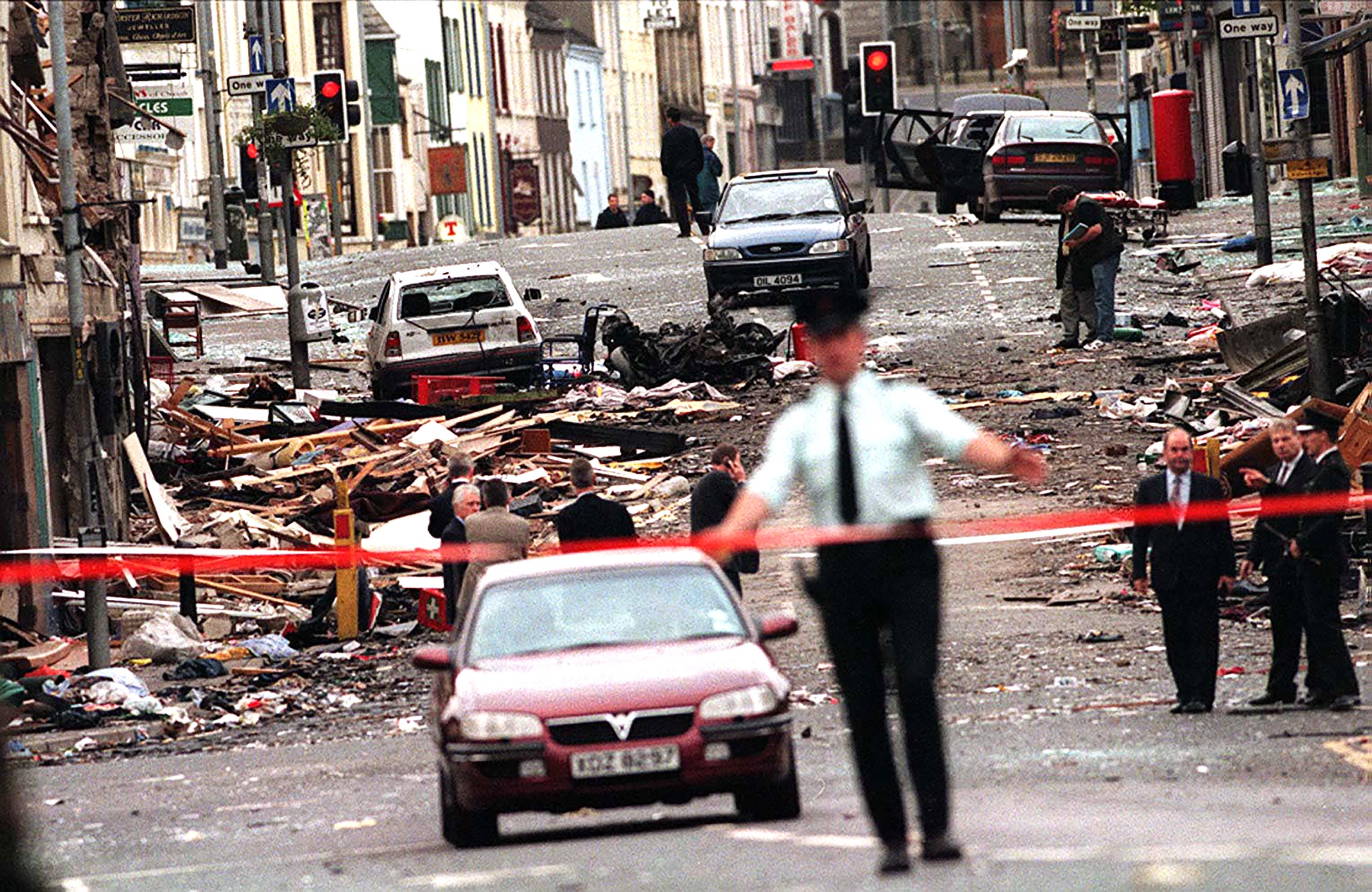 A soldier standing close to a building that has been destroyed by a bomb during the Troubles