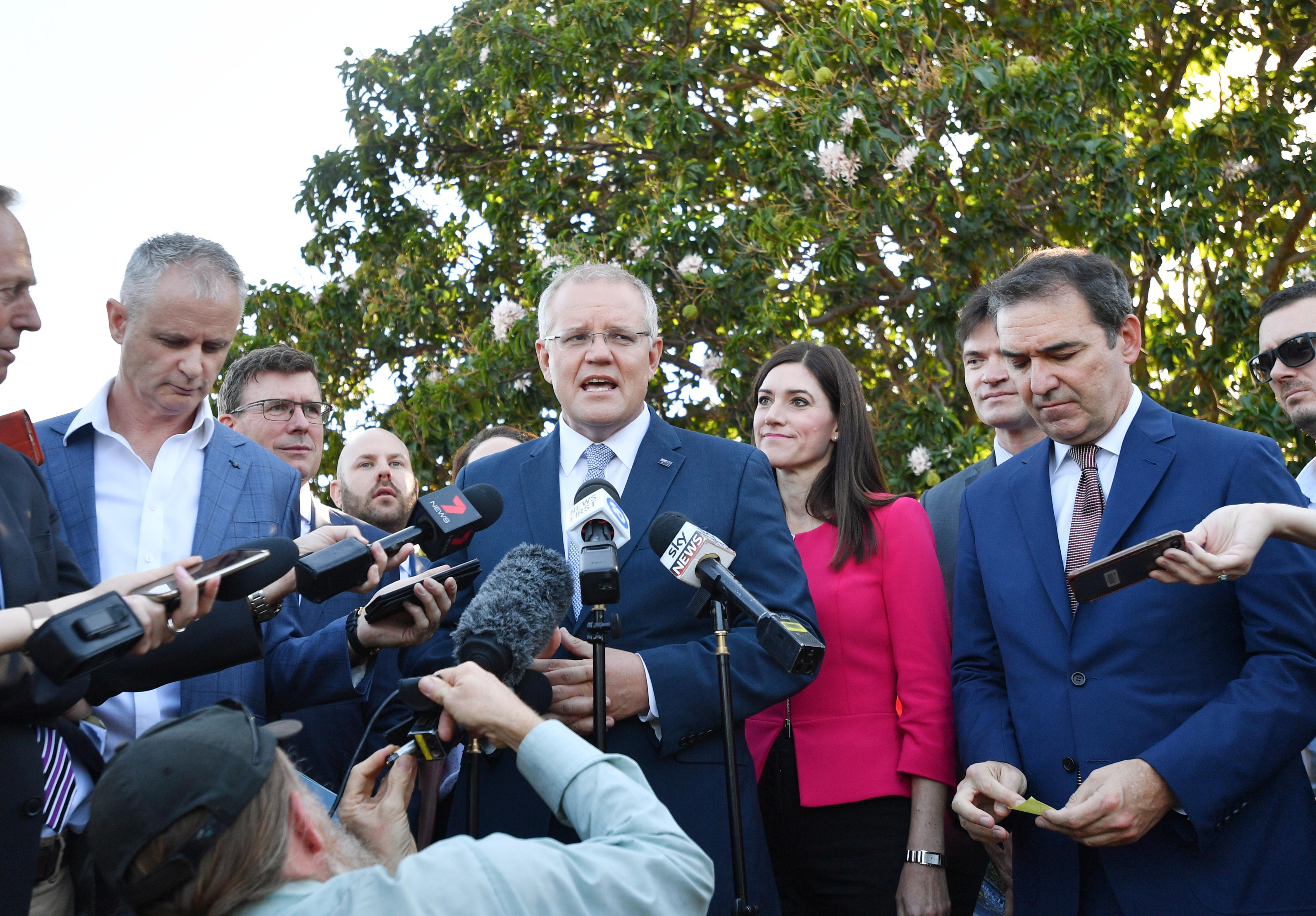 Australian Prime Minister Scott Morrison (C) speaks in Adelaide on 19 March