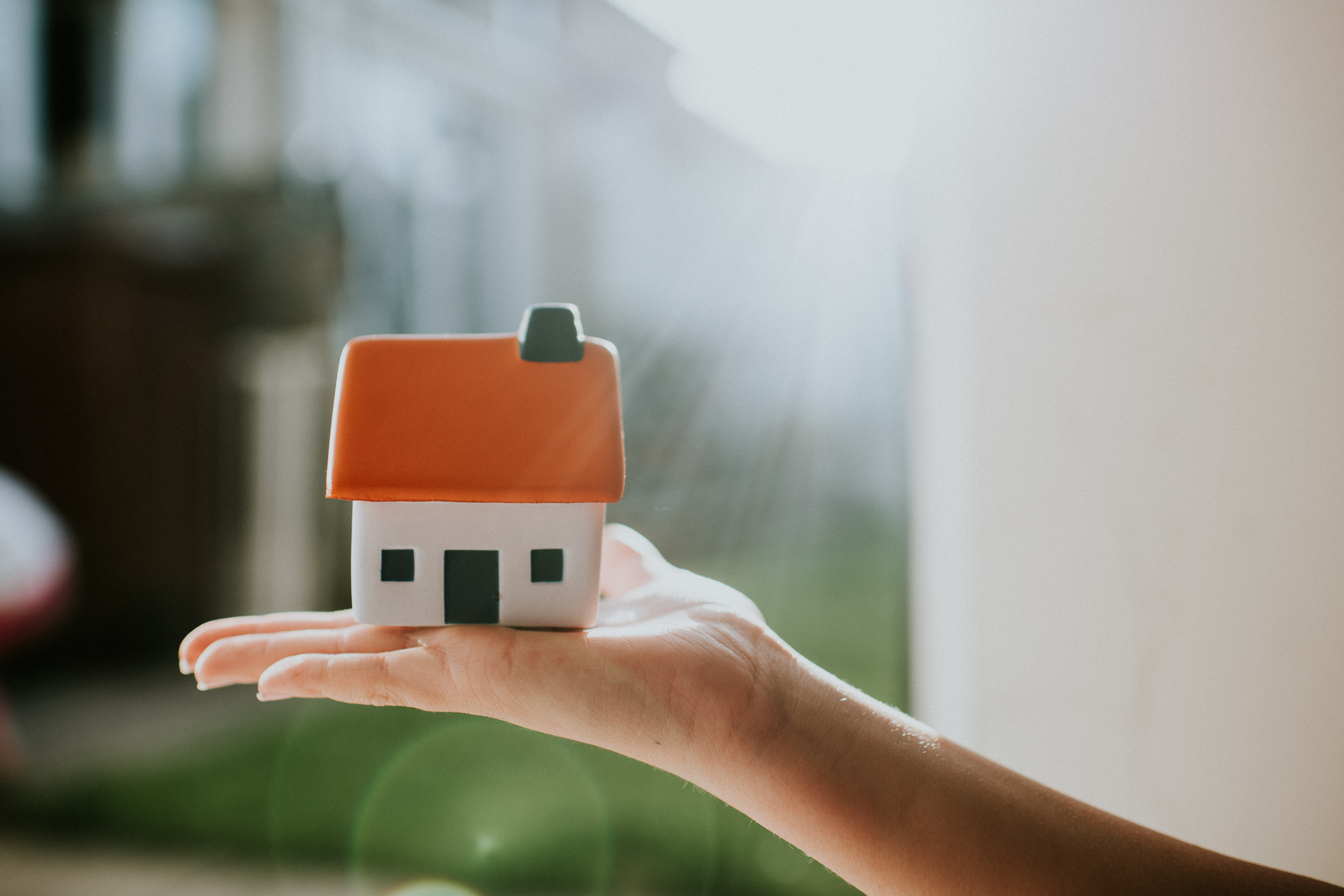 Casa en miniatura sobre una mano.