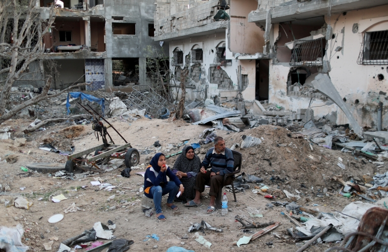 Palestinians sit near destroyed houses in the northern Gaza Strip (1 June 2021)