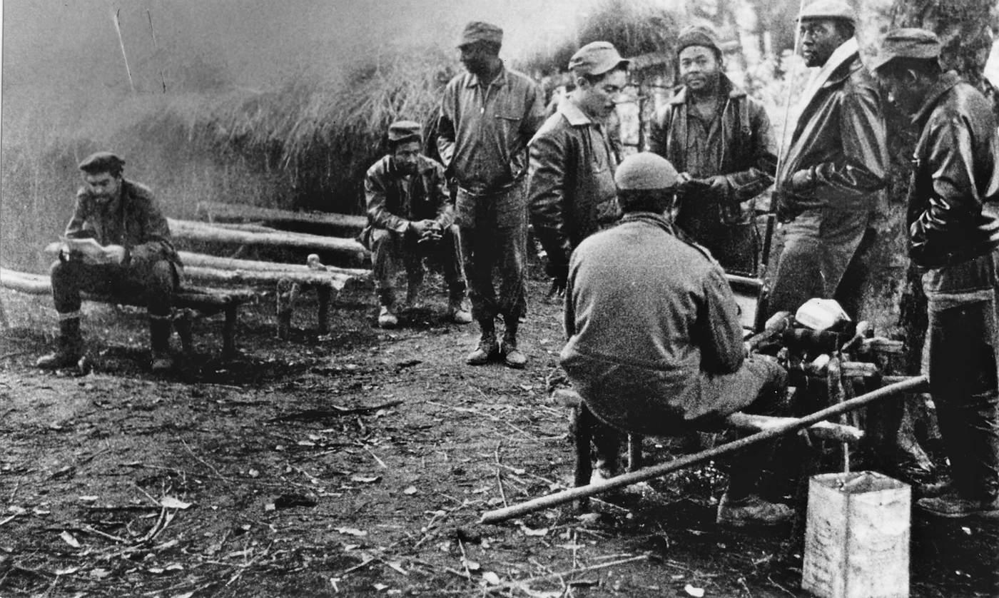 """Ernesto Che Guevara con guerrilleros congoleños y cubanos en un campamento en la selva africana. Más tarde el Che escribirá un diario sobre su experiencia en Congo, publicado en Cuba por primera vez en 1999 con el título """"Pasajes de la Guerra Revolucionaria, Congo""""'. (AFP\/Getty Images)"""