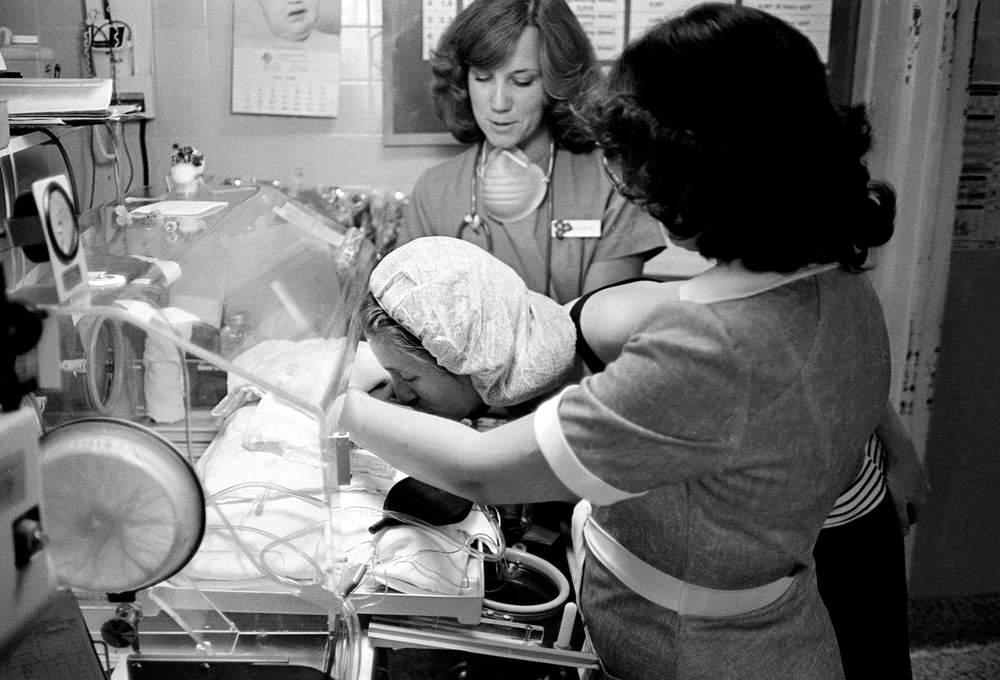 Mother kisses daughter in incubator, Arizona, 1980, Hurn.