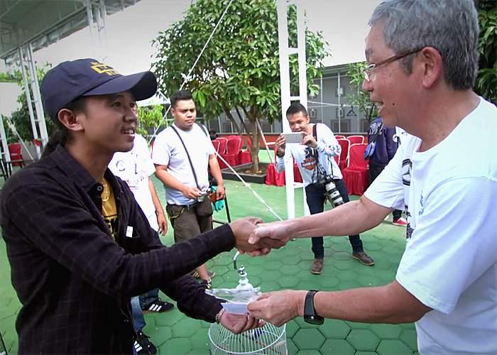 Tony Sumampau presents a prize to a winner
